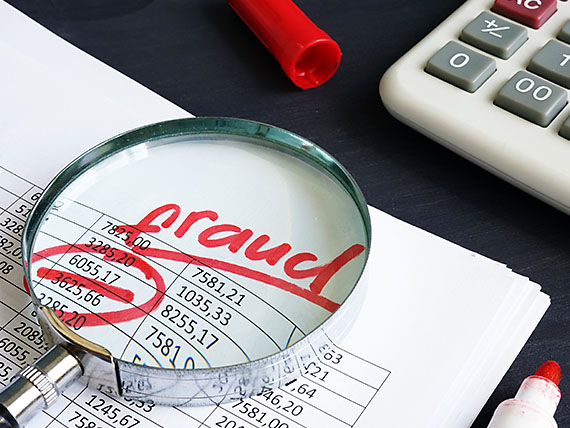 The word Fraud seen using magnifying glass