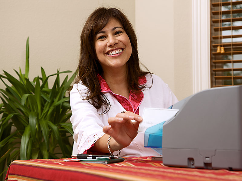 Business woman using Remote Check Scanner